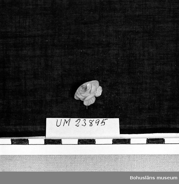 594 Landskap BOHUSLÄN  Skuren ur tand i form av ros. Tillhör dockan Adéle.  Personuppgifter; se UM23863.
