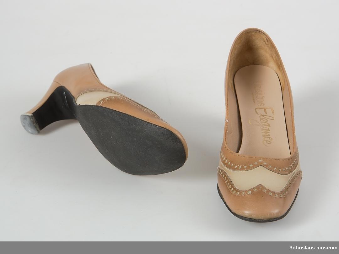 """Pumps i ljusbeige och ljusbrunt läder med dekorativa kanter kring läderstycken. Tryck i insidan i guldbokstäver: """"Elegance""""."""