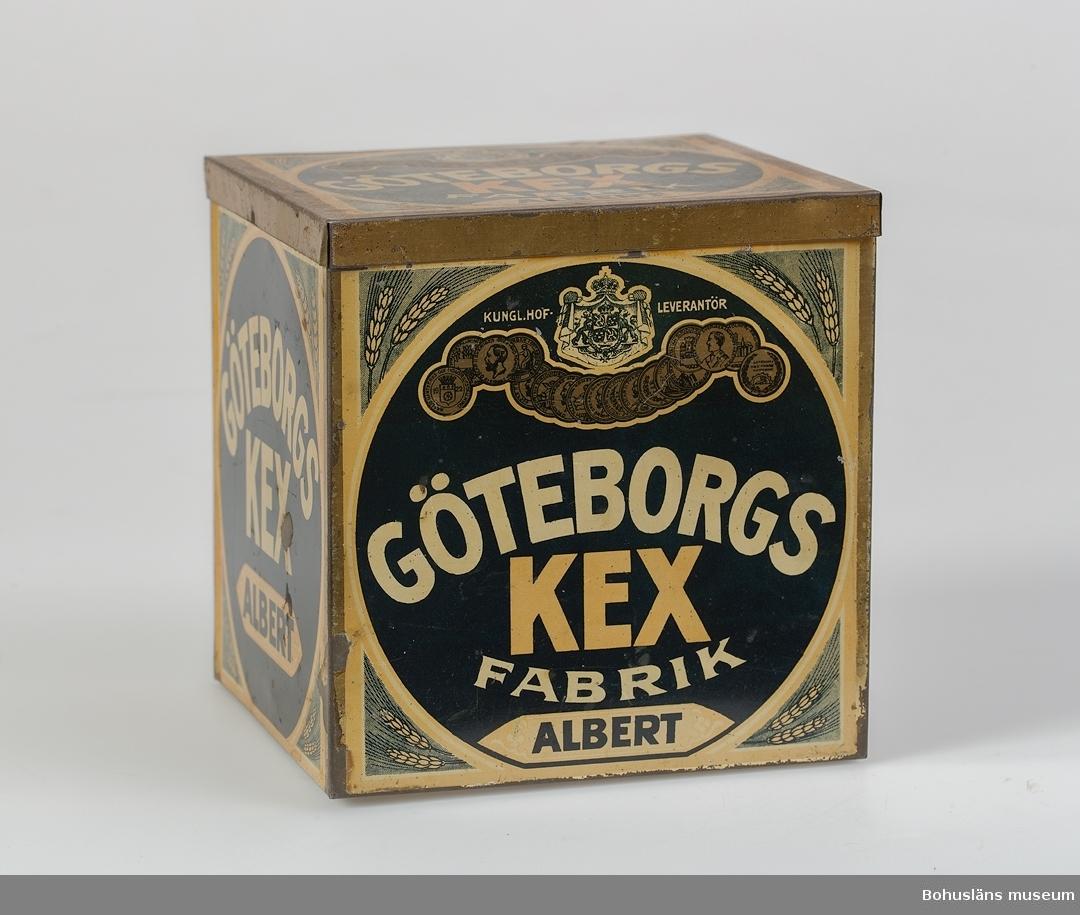 """Locket sitter fast i ena sidan. Text på alla sidor. Text på locket """"KUNGL. HOF. LEVERANTÖR GÖTEBORGS KEX FABRIK ALBERT"""". När burken kom till museet låg det julgransljushållare inuti se UM024721 - UM024726. Tidigare funktion: Förpackning för den saltade kexsorten Albert. Kex av detta slaget såldes också i enklare pappersförpackning; kunde ätas som tilltugg vid kaffestunder.  Saxat ur programmet """"Släktband"""" i Sveriges Radio P1 i januari 2006 som handlade om skottar invandrade till Västsverige. Den skotska familjen Cruickshank kom till Sverige år 1888. De bosatte sig i Kungälv och var delaktiga i starten av fabriken Göteborgs Kex. Familjen bestod av Robert och Margaret Allison Blair McKimmie Cruickshank samt fyra söner och en dotter. Ättlingarna och bröderna David och Tomas Hedberg berättade om sin anfader som kom hit med två kexrecept på fickan, ett sött och ett salt. Det söta blev Mariekex och bildade basen för en hel industri. Det salta kexet gick under benämningen Albert. Kanske var det också familjen som lärde arbetarna på kexfabriken att spela fotboll. Det berättas att man slet ut kläderna på det nya spelet. Officiellt pratar man om att det var i Göteborg år 1892 som man först i landet spelade fotboll.  När Robert Cruickshank vid 51 års ålder kom hem från fabriken en lunch satte han sig ner, tog en klunk whiskey och drog ett bloss på cigarren. Sedan sa han till sin son: """"John I'm fainting"""". Därefter satte han ned glaset och dog. Änkan Allison Blair McKimmie Cruickshank levde fram till 1906 .   Information från familjen Cruickshanks hemsida på Internet i januari 2006: Orsaken till familjen Cruickshanks flytt till Sverige var att skeppsredaren och affärsmannen Carl Leopold Berggren i Göteborg ansåg att det borde finnas en marknad för svensktillverkade kex. Han var gift med en engelska och var därför van vid att det serverades kex till både te, sherry och portvin. Och i Göteborg fanns det gott om köpmän med brittiskt härkomst som importerade kex och sålde dem vidare"""