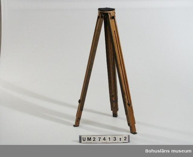 594 Landskap Bohuslän  En reskamera i trä (:1) med utfällbart, trebent stativ (:2),  löst objektiv i träfodral, fabrikat WASA FOTO-MAGASIN GÖTEBORG. DUBBELANASTIGMAT 1:6,8 F = 240 mm (:3)  samt en svart duk (:4).  John Carlåhs arbetade som kontorist på Systembolaget i Uddevalla. Han var en duktig amatörfotograf och har bl.a. vunnit pris i Uddevalla Konstförenings fotografitävlan 1930.  Han var även amatörmålare. Han var också intresserad av arkeologi och samlade föremål av flinta. Han ägde den största privatsamlingen i Bohuslän. (Okänt varifrån denna uppgift härstammar.) En del av detta är skänkt till Bohusläns museum.