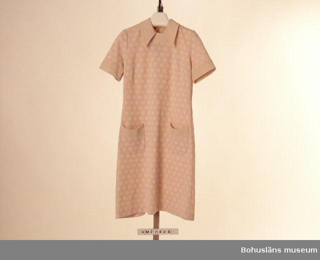 """Föremålet visas i basutställningen Uddevalla genom tiderna, Bohusläns museum, Uddevalla.  Mönstrad klänning med kort ärm med rosa/vita blommor på beige botten och med detaljer - krage, halsringning, ärmkant och fickkanter - i enfärgat beige tyg.  Rak, enkel, något utsvängd modell. Rund  halsringning med krage.  Bystveck. Utanpåliggande svagt rundade fickor med enfärgad, rak kant. Tvåvådigt bakstycke med lång dragkedja i mitten som avslutas i kragen som är nedvikt bak. Ofodrad. Modellen är """"Mary Quant-inspirerad"""". Etiketter i halslinningen med med texten: """"Magna 40"""" respektive """"Crimplene & Terylene med bomull With cotton Mit baumwolle"""".  I dragkedjan vidhängande pappersetiketter i silkessnöre med texten: """"Magna"""", andra sidan: """"Modell A 92 Kvalité 152 Färg 1 Storlek 40 Varuinformation ter. 85%  bom. 15% Pris  289:-"""" Vid platsen för pris har Prylmarknaden fäst en klisterlapp med texten """"Kr 45.-"""" Obegagnad vid förvärvet.  Ur Nationalencyklopedin, NE.se: Terylen Terylen, en skrynkelhärdig textilfiber framställd av polyester urspr. varumärke, sedan 1955; av eng. terylene med samma bet.   För ytterligare uppgifter om förvärvet och övrigt material rörande Magnafabriken i museets samlingar, bl.a.  dokumentation 1998, se UM027416."""