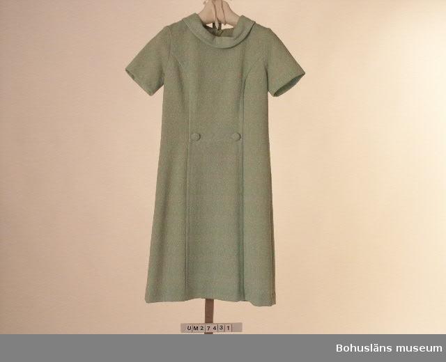 """Föremålet visas i basutställningen Uddevalla genom tiderna, Bohusläns museum, Uddevalla.  Ljusgrön klänning med kort ärm och smal, nedvikt schalkrage med snibbar i nacken. Tyget är mönstrat i grått och vitt i svag relief på ljusgrön botten. Framstycket i tre våder där det mittersta är avskuret i midjan och markeras av två klädda knappar. Bakstycke i två våder med en 50 cm lång dragkedja i mitten. Långa insparningar på ömse sidor. Ofodrad.  Etiketter i halsringningen med med texten: """" 'Magnalene' 100 CRIMPED POLYESTER 38"""" Saknar pappersetikett. Obegagnad vid förvärvet.  Denna klänning är """"à la Jaqueline Kennedy"""", som var en av 1960-talet förebilder inom modevärlden.  För ytterligare uppgifter om förvärvet och övrigt material rörande Magnas produktion i museets samlingar, bland annat dokumentation 1998, se UM027416"""