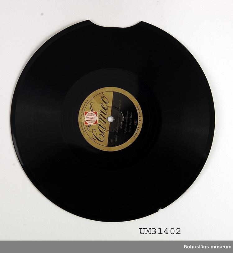 Grammofonskiva, stenkaka i papperfodral.  Ena sidan: Calle Schewens vals. Evert Taube. Sjömanspojkarna.  Andra sidan: Fritiof Anderssons paradmarsch. Evert Taube. Sjömanspojkarna.  Skivmärke: Cameo  Grammofonskivan som ingår i skivsamling som spelats i en sommarstuga i Sundsandvik, byggd 1939. Skivorna spelades på en svart resegrammofon, se motsvarande modell UM026268. För ytterligare upplysningar om förvärvet, se UM031385.
