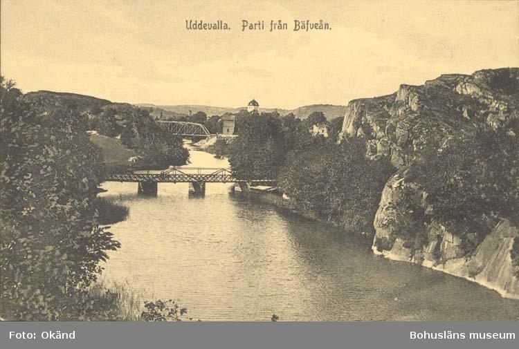 """Tryckt text på kortet: """"Uddevalla. Parti från Bäveån."""" """"Förlag: J. F. Hallmans Bokhandel, Uddevalla."""""""