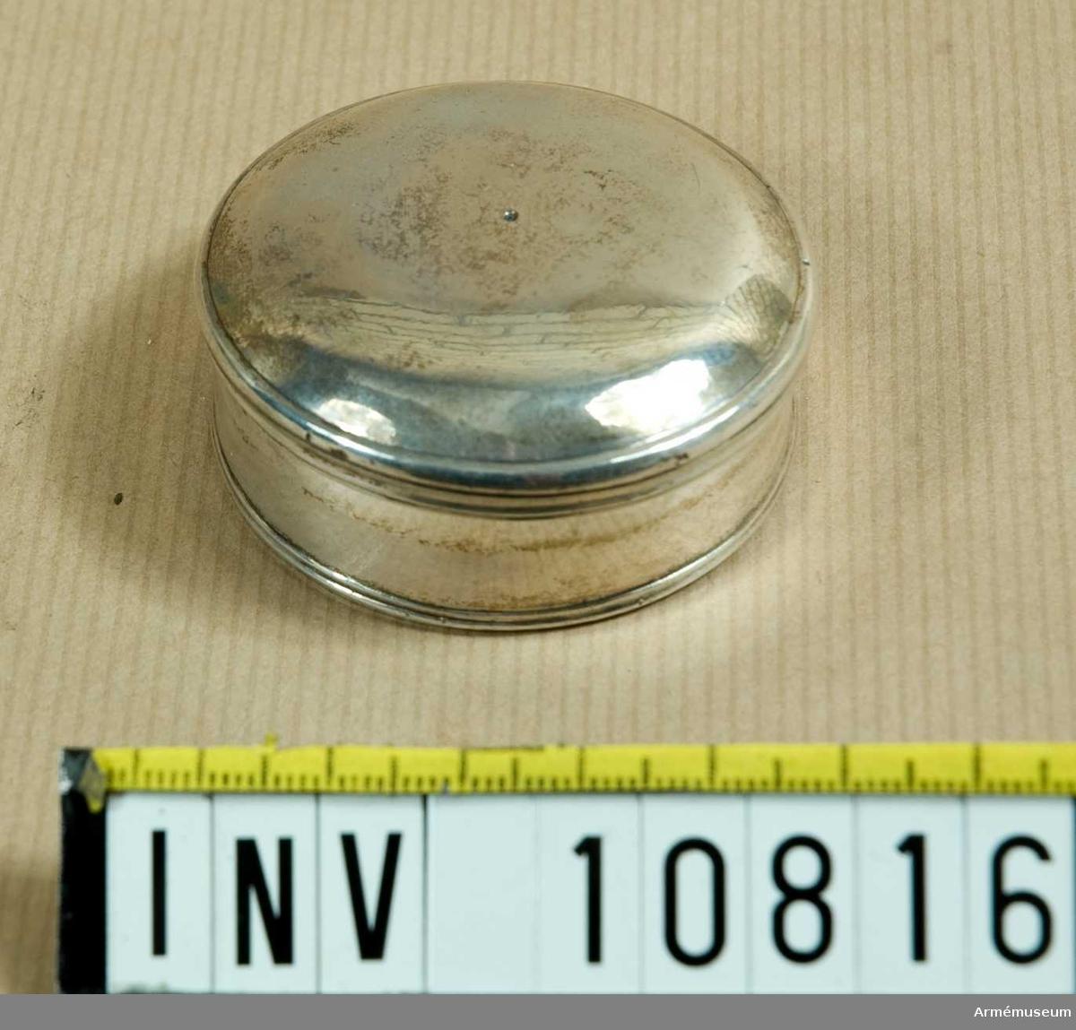 """Grupp B II. Rund oblatask av silver 4 3/8 lod. För sjukbesök och för  Kungliga Artilleriregementet. Tillverkad år 1735 i Stockholm.Förvarades P 2 1974.1991-03-08 rengjord med """"guldtvätt"""" (AM:s recept) bestående av  såpa 125 g, sprit 95 % denaturerad 115 g, ammoniak 5 mol/l 230  g, oxalsyra 35 g, vatten renat 1300 g. Därefter väl sköljd.  Sedan lätt putsad med Duraglit / Kjell Hedberg & Göran  Askebrandt."""