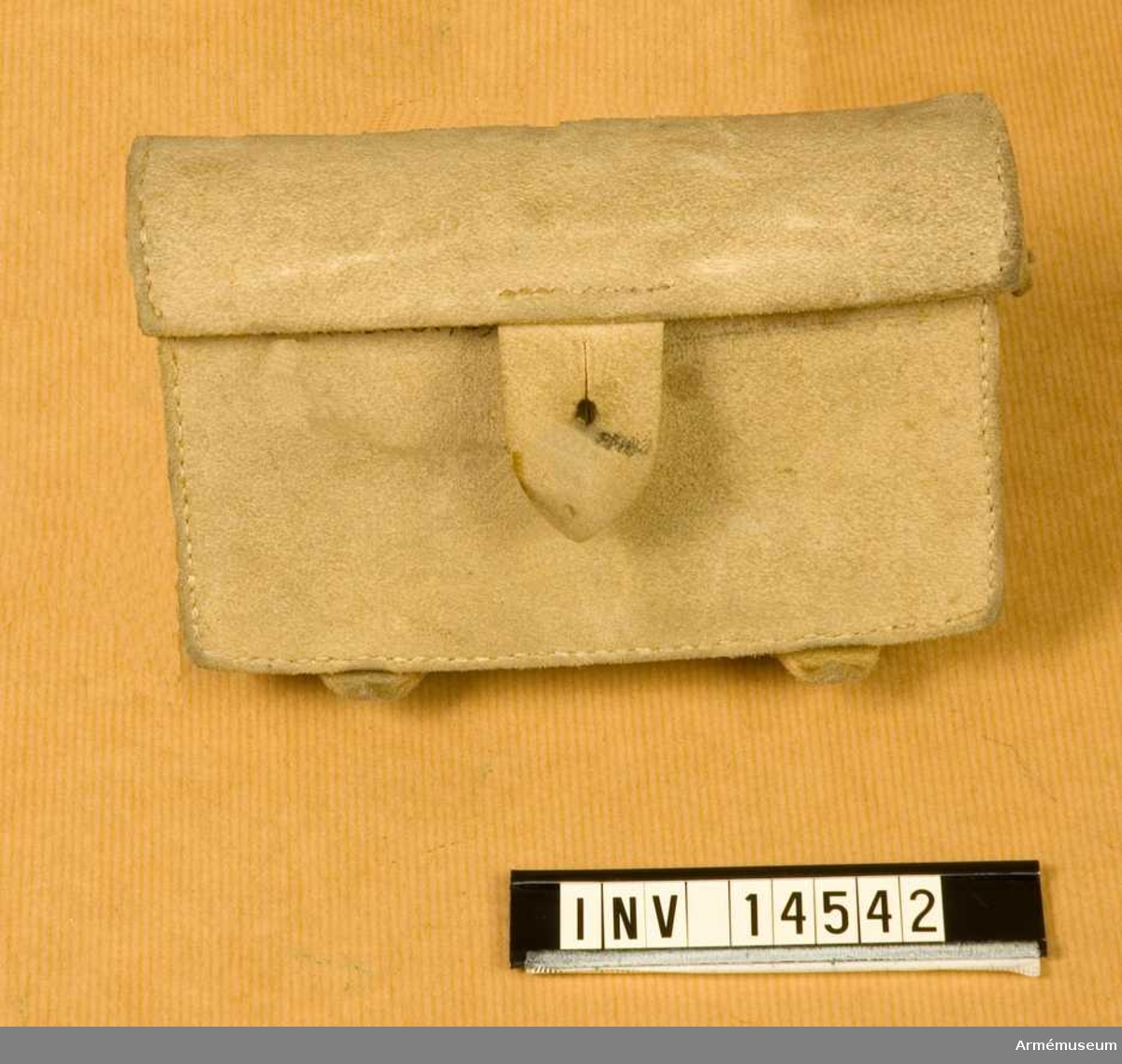 """Grupp C:I. Patronväska av älgläder, består av lock med en läderbit som har knapphål och stängs på framsidan. På lockets baksida står: """"England"""". På väskans framsida en knapp för knäppning - och på baksidan två hylsor av samma läder, för att fästa den vid livremmen. I väskan finns järnfodral med mellanvägg också av järn. På väskans baksida stämpel """"W L D"""" - över L en uppåtriktad pil. Litteratur: Enl. Die Englische Armee. Leipzig. Verlag von M. Ruhl, sid 20. Infanterie. Das Lederzeug. Remtygspersedlar voro av vitläder. Bilaga sid 4, 5, 6, 7, - alla gardes- och linjeinfanterister ha vita remtygspersedlar. Handbuch der Uniformkunde. Prof. Rickard Knötel. Hamburg 1937. Sid 197. Infanteriet har vita remtygspersedlar utom skarpskytteregementenas som bära svarta. Die Heere und Flotten der Gegenwart. G. von Zeppelin. Berlin. 1897. Sid 25. Utrustningens remtygspersedlar består av vita läderremmar.Samhörande nr är 14534 lägermössa, 14535 vapenrock, 14536 byxor, 14537 fältflaska, 14538 ränsel, 14539 livrem, 14540 skor, 14541 och 14542 patronväskor."""