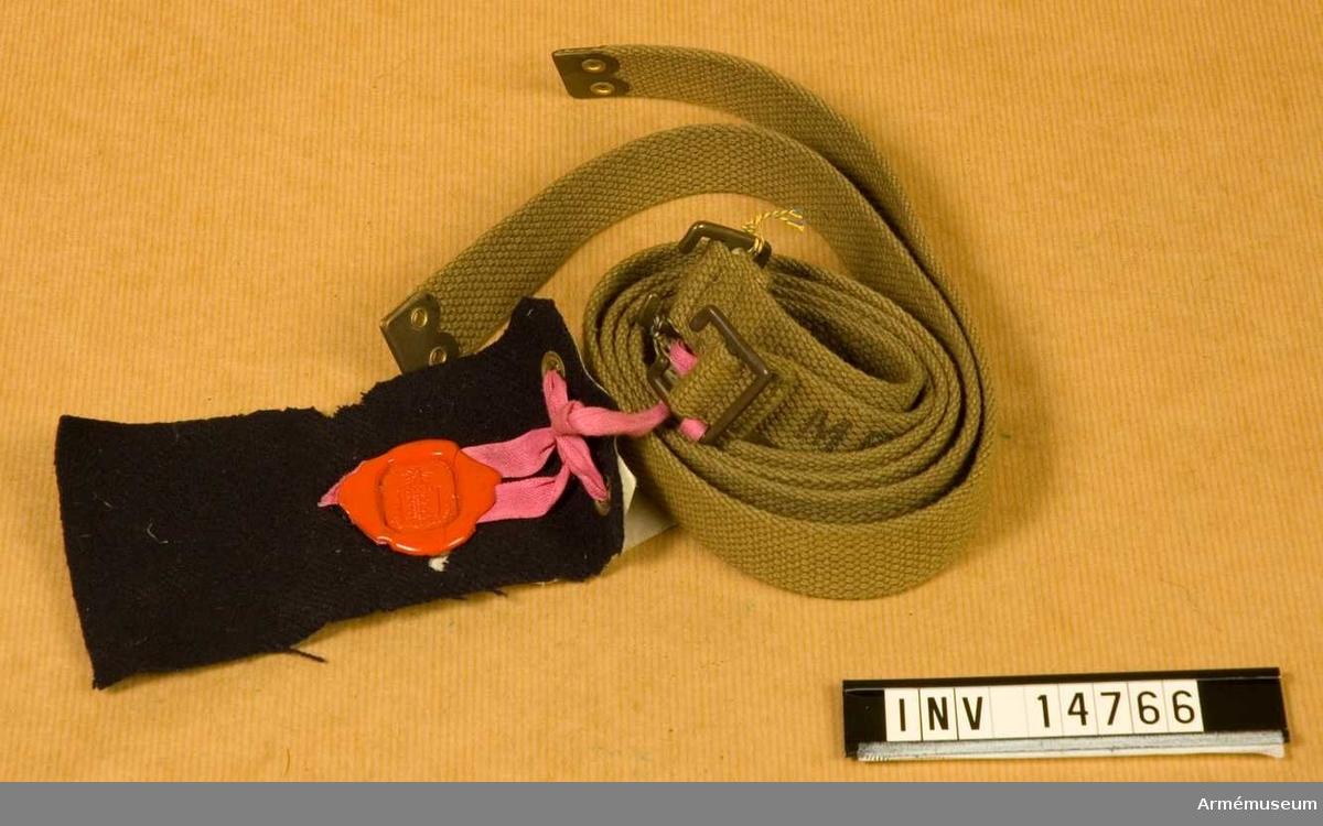 """Grupp C I Bärremmar till tornister. De är av tjockt bomullsband, khakifärgade, 2,5 cm breda. På ändarna spännen och beslag av mässing. Båda bärremmarna har stämplar: """"M.E.Co.1911"""" och uppåtriktad pil över """"10""""."""