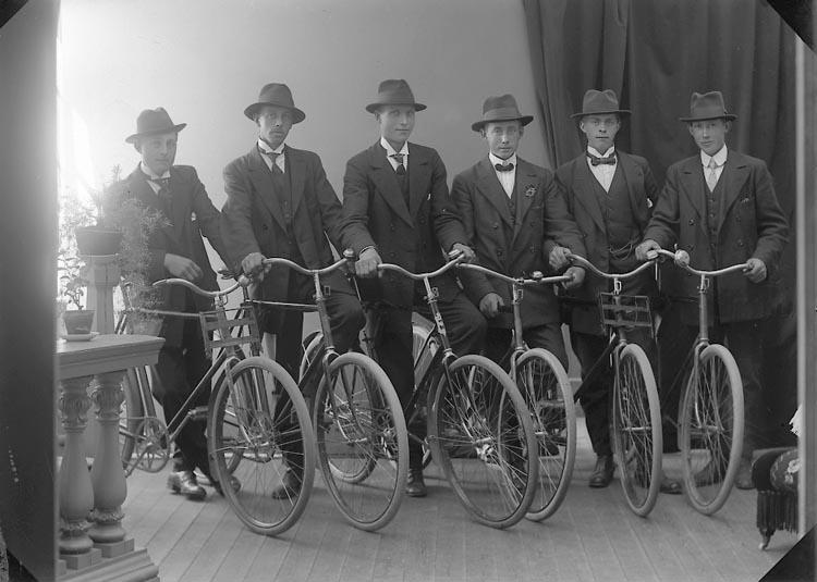Sex män porträtterade tillsammans med sina cyklar i en fotoateljé