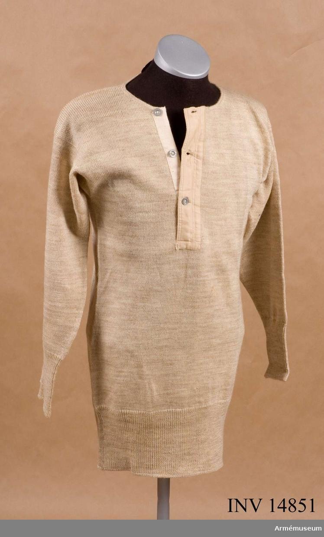 Grupp C I Av beige yllegarn med långa ärmar. På bröstet finns ett sprund, som knäppes med tre järnknappar.