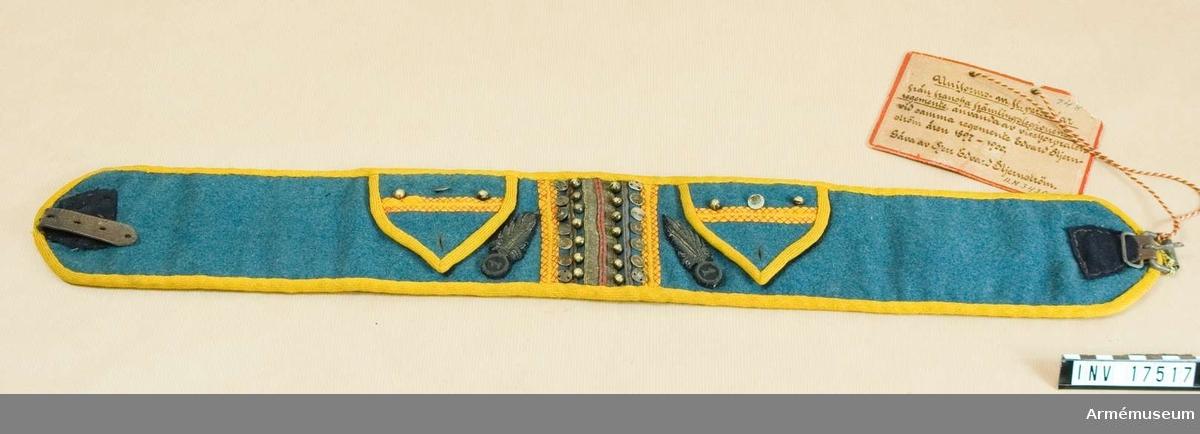 """Grupp C I. Ur uniforms- m fl persedlar från franska främlingslegionen. Buren av givaren som vicekorpral vid 1 regementet av franska främlingslegionen 1897-1900. BÄLTE (la ceintur) av ljusblått kläde med fastsydda läderremmar i ändarna. På en av remmarna järnspännen. Bältets framsida har två fickor, en för klocka och den andra för pengar. Bältet och båda fickorna är omsydda med gula flata och kullriga, små knappar. Sidorna har broderier på svart kläde i form av flammande granater med nummer (första regementet) i mitten. Bältet är fodrat med mörkblått kläde.  Anteckning, troligen lämnad av givaren: """"'Les ceinture'. Bältena. Dessa hör strängt taget inte till soldatutrustningen utan fick av soldaten själv anskaffas och betalas. De var emellertid tämligen nödvändiga, för soldaten har inget annat ställe att förvara klocka och pengar än i deras fickor. Den blåa breda gördeln är tillverkad av arabkvinnor i Figuig (syd Oran)."""""""