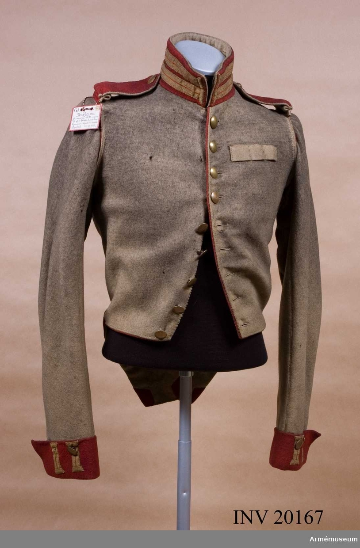 Grupp C I. Ur uniform m/1820-40 för menig vid Livgardet till häst, Andra regementet 1. Gardets kavalleridivision. Frack av vitt kläde. Enkelknäppt med röd passpoal och nio flata mässingsknappar. Axelklaffar av rött kläde med vitt underkläde, fastsydda i ärmsömmen och fastknäppta med en mässingsknapp. Foder av grov linnelärft. Krage av rött kläde med 2 knapphål av gula redgarnsband, fodrad med vitt kläde och sammanknäppt med tre  hyskor och hakar. Passpoal av rött kläde vid knäppningen runt nederkanten och i ärmsömmarna. Skört med 2 diagonala, röda lister, b:35 mm. Markerande, obefintlig uppvikning i listernas skärningspunkt. Ärmuppslag av rött kläde med två knapphål av gult redgarnsband och två mässingsknappar.  LITT  Pantschulitseff, Chevlaliergardets historia, del III, sida 406: enligt dagorder. No. 211 den 20 maj 1814 från krigsministeriet infördes enradig kollett med nio knappar. F von Stein Geschichte des russischen Heeres, Hannover 1885, sida 325. Arme Russe, 1855, Pajol, sida XXIII-Regiments uniform.