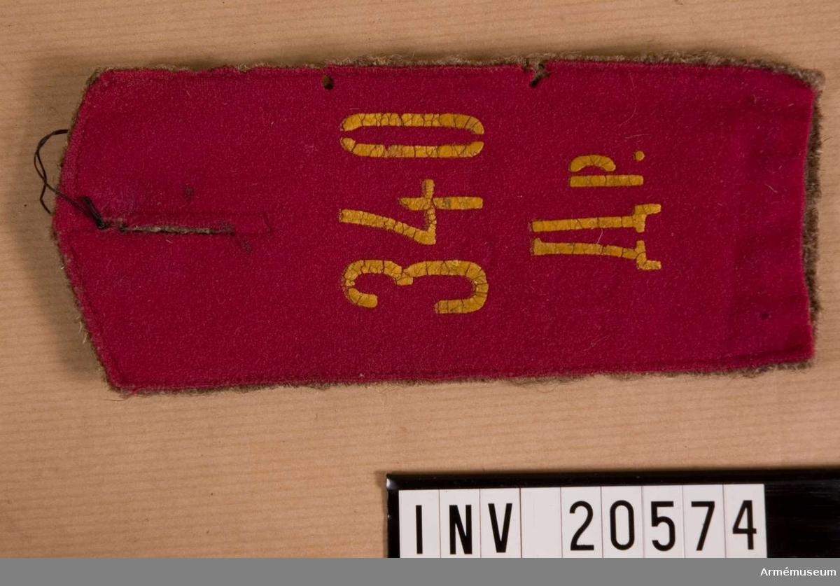 """Axelklaff för menig landsstormssoldat vid 106 Reservinfanteriregementet, Ryssland. 1914. Grupp C I. Av rött kläde med ett hål i mitten för knapp. Foder av gråbrunt kläde. Siffran 106 målad i mörkbrun färg, 106. reservinfanteri- reg:t. Siffra i gul färg och rysk text, se bilaga, på sv. """"340. bataljon"""". Annan rysk text betyder bataljon och används endast för 340. landstorms druschina eller 106. reservinfanteriregementet existerade under världskriget 1914-18."""