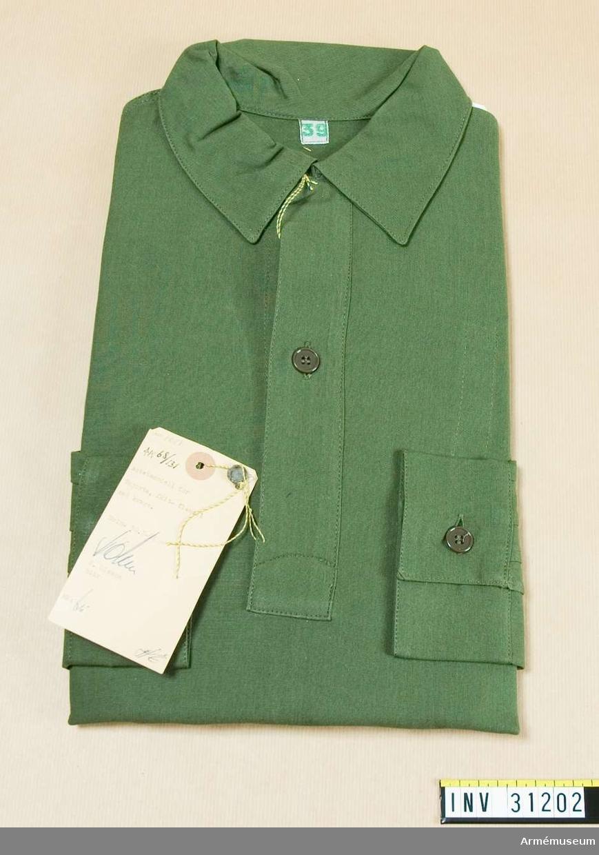 Samhörande nr 31200-5. Fältskjorta med krage. Grupp C I. Ur uniform m/1958 för förvaltare vid kavalleriet.  Består av rock, fältbyxa, fältskjorta, livrem m/1952, bälte, marschpjäxor.