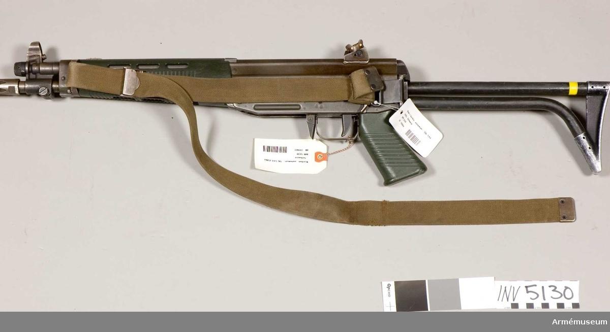 Tillverkningsnummer 10253.  Längd axelstödet i infällt läge 580 mm. Pipans längd med mynningsbroms 328 mm. Vapnet märkt med (SIG) SG 543. Bestående av: 1 st automatkarbin, 1 st gevärsrem av väv.