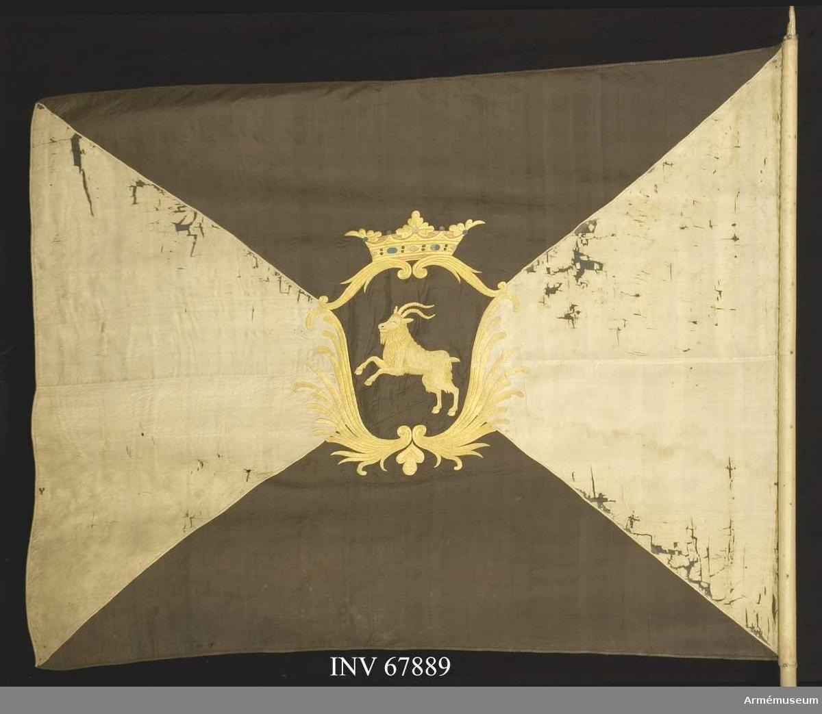 Duk: Fyrstyckad, tillverkad av enkel svart och vit sidenkypert. De vita fälten sydda av två våder.  Dekor:  Broderad - en sköld av stiliserade palmkvistar i gult silke, krönt av en öppen krona i gult silke med foder i rött och stenar i rött och blått silke. Däri Hälsinglands vapen: en bock i gult silke på ett fält av svart siden. Broderierna utförda i dubbelsidig plattsöm.  Kantad med sidenband, vitt på de vita fälten, svart på de svarta.    Fäst vid stången med förgyllda spikar på vitt sidenband. Stång av vitmålad furu. Saknar spets och holk.