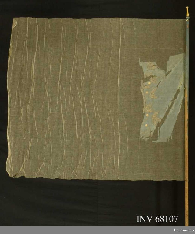 Duk: Tillverkad av enkel blå sidentaft, sydd av två horisontella våder. Duken fäst vid stången med en rad tennlickor på ett blått kypertvävt band.  Dekor: Målad lagerkrans i silver med bär i guld.   Stång: Tillverkad av furu, målad ljusbrun. Holk av mässing.