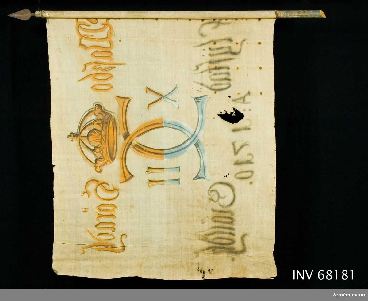 Duk: Tillverkad av enkel vit linnelärft. Två våder horisontellt sammankastade (kastfåll åt dukens insida). Vertikala ytterkantsfållen åt dukens insida. Fäst med stora järnnaglar.  Dekor: Målad endast på dukens insida dock är namnchiffret och kronan ifyllt på dukens utsida. I mitten Carl XII:s namnchiffer krönt med sluten krona, dubbelt C, på ömse sidor om detta X-II. På övre våden i gult och brunt på den nedre i svart och blått.  Text på ömse sidor om chiffret, upptill i gult och nedtill i svart. Under chiffret text i svart.  Stång: Tillverkad av trä, blåmålad. Snett avsågad nedtill. Iskruvad lansettformad spets. Gängad tapp.