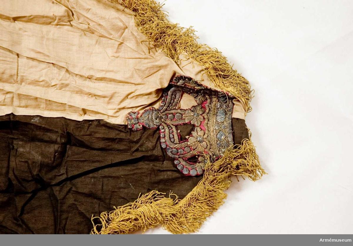 Duk: Tillverkad av enkel gul och svart bomull. Fäst upptill i ena hörnet, hopveckad (ev. tillfälligt hopkommen). I det nedhängande hörnet applicerat en broderad krona, klippt ur en röd fana. Duken troligen felaktigt monterad.  Frans, enkel, av gult silke.  Stång: Tillverkad av trä, gulockramålad. Kannelerad. Klädd med tyg och frans i övre delen. Nederst blått tyg, över detta gult tyg.