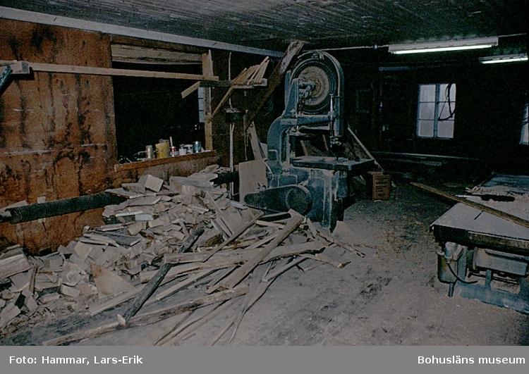 """Motivbeskrivning: """"Kungsvikens jakt och Motorservice, (Gösta Johansson), Kungsviken, Orust. Interiör från båtbyggarverkstaden."""" """"Interiör från båtbyggarverkstaden. På bilden syns en bandsåg.""""  Datum: 1978"""