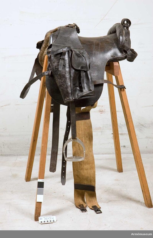 Grupp K: I. Pistolhölster till sadel; 1856. Samhörande: Sadelgjord av väv, övergjord av läder. 1. par stigbyglar. 1. par stigläder. 2. packfickor, den ena med pistolhölster.