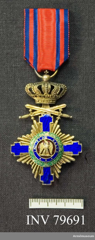 Grupp M.   Ett gyllene, med blå emalj belagt grekiskt kors (dock något närmande sig ett kryckkors), ovanpå vilket äro placerade två korslagda svärd med fästena nedåt (svärden angivande, att ordenstecknet är förlänat för militära förtjänster) ; därovanför en stor. rörlig kunglig krona med äpple och kors överst.  Genom äpplet är trädd en ring för bandet. Åtsidan: Mittpartiet upptages ytterst av en lagerkrans i grön emalj, ombunden på fyra ställen av gyllene band, därinnanför en guldkantad ring av blå emalj, å vilken med inlagda guldbokstäver läses: INTIDE SALUS jämte, nederst, tre små femuddiga guldstjärnor. Allra innerst ett runt parti av mörkröd emalj, varå synes, i stark relief, en gyllene örn med utspända vingar. Mellan korsets armar frambryta gyllene strålar av olika längd, symmetriskt ordnade. Frånsidan liknar åtsidan beräffande korsets armar och lagerkransar, men strax innanför dessa vidtager ett parti af purpurröd emalj, på vilket, i starkt upphöjt arbete synas i monogram två, från varandra vända, rikt utsirade C; i deras korsning: I samt ovantill en kunglig krona. Bandet: purpurrött med två smala mellanblå kantränder å vardera sidan.