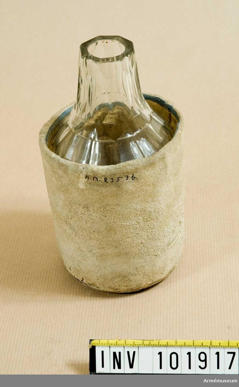 Flaska av slipat glas för nattvardsvin. Skyddsfodral av sämskskinn. Naturkork.