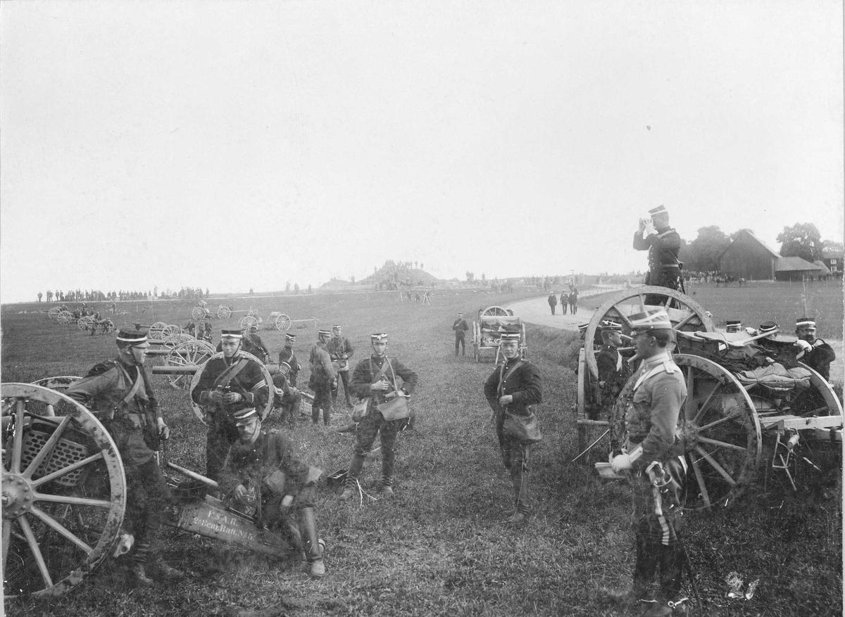 Svea artilleriregemente, A 1, uppställda för fälttjänstövningarna i Närke 1895. Manskap och officerare stående bland 8,4 cm kanoner m/1881-1894. I förgrunden löjtnant R. von Rosen, K 1, volontär Hazelius med 3 streck på ärmen.