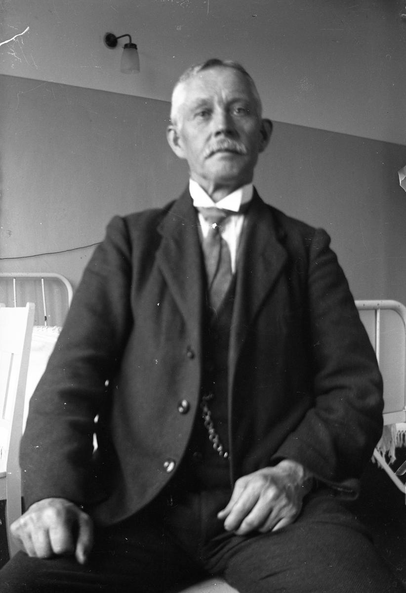 Lungkliniken i Eksjö. En man med mustasch sitter på en stol, i bakgrunden syns en sjukhussäng.