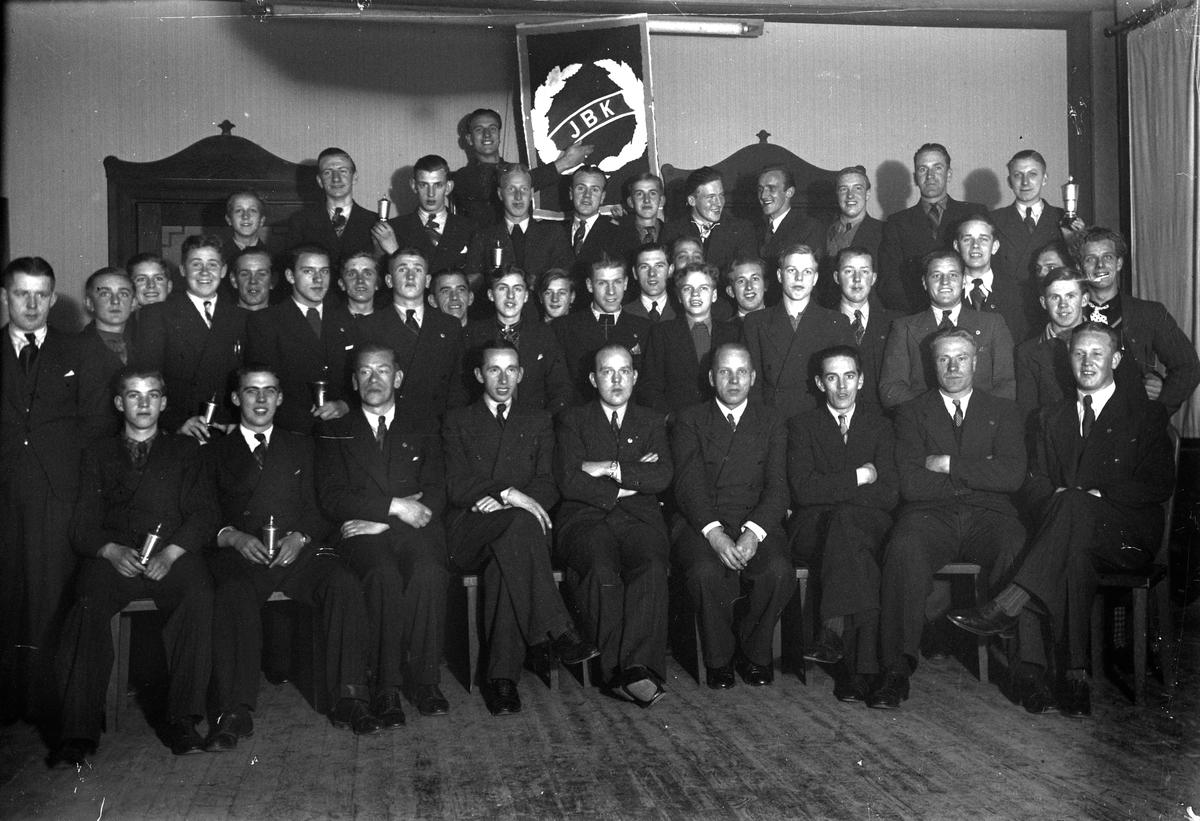 44 män och pojkar står eller sitter med en vägg som bakgrund. En man håller en tavla med motiv av en krans och bokstäverna JBK.