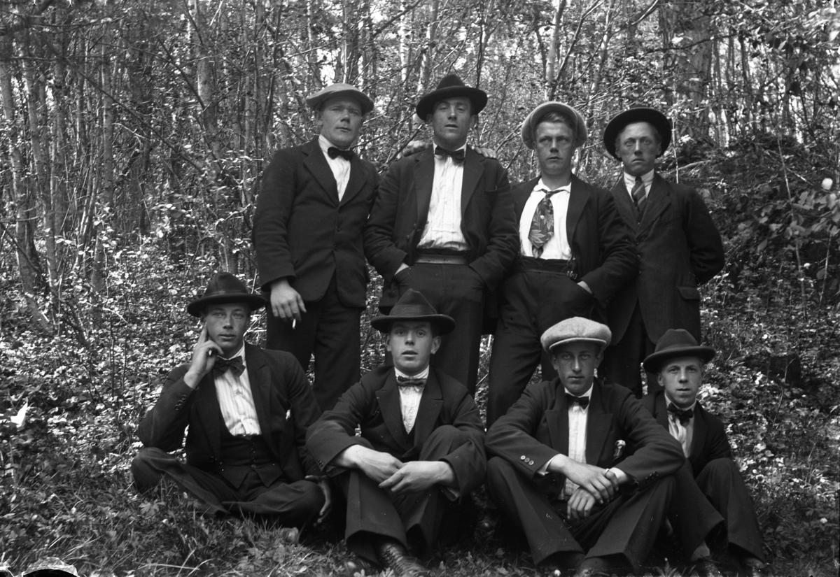 Fyra män står och fyra sitter på marken i skogen.