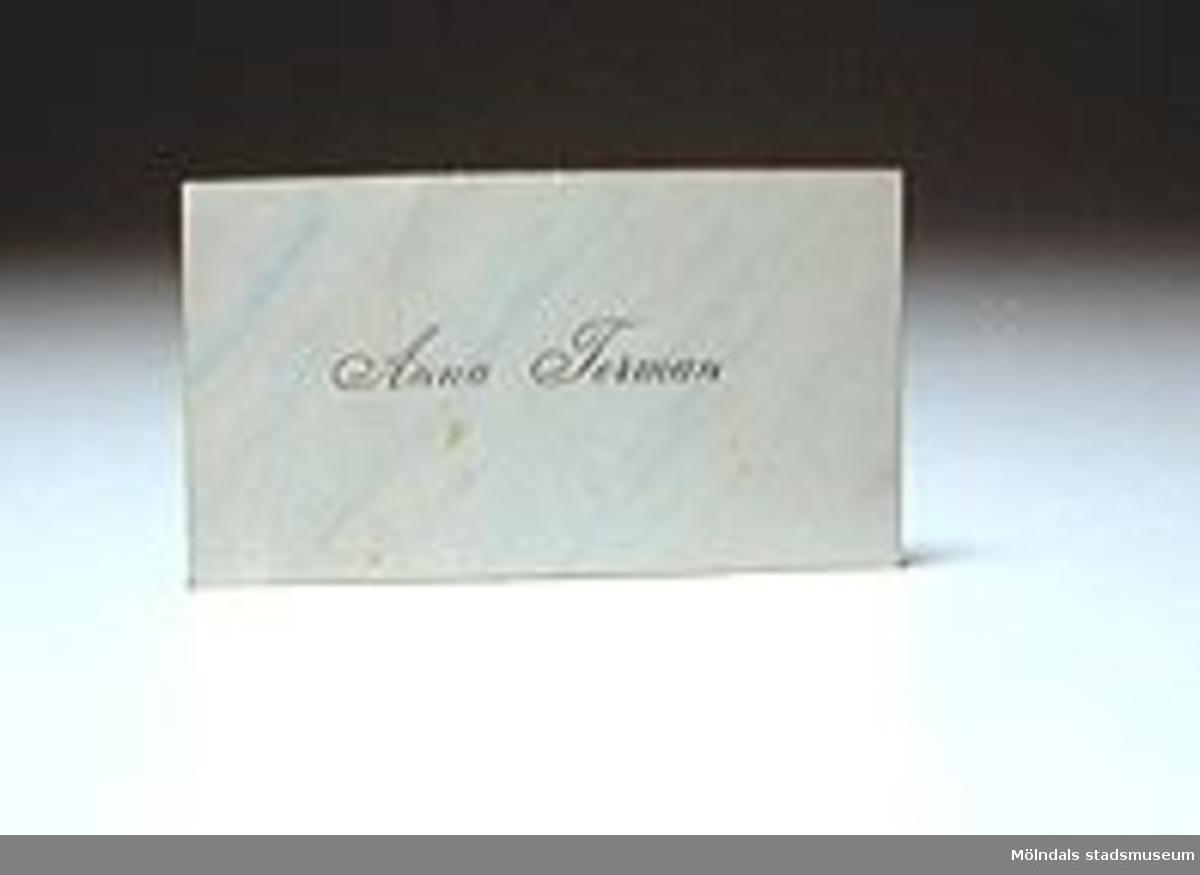 Visitkort märkt Anna Torman i skrivstil på en blåvitmelerad bakgrund.