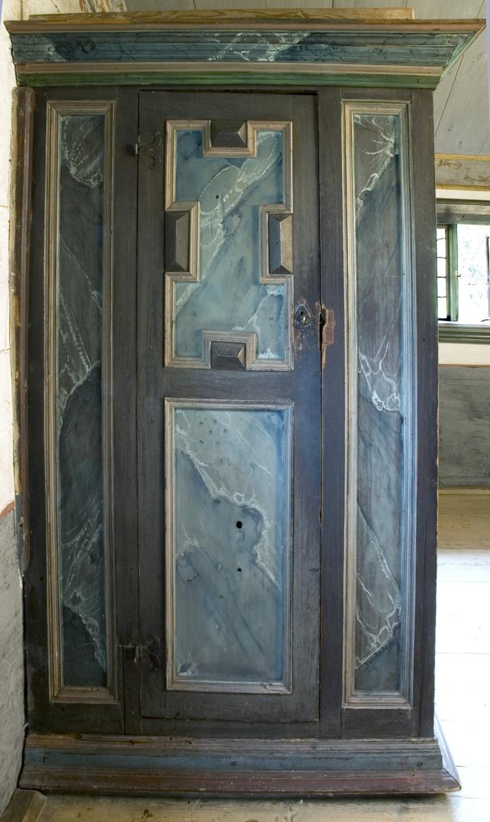 Skåpsäng av trä, platsbyggd. Bred profilerad rak krönlist. Fotänden med skåp, speglar på var sida om skåpdörren samt två speglar vända ut mot rummet. Skåpdörren har två speglar, den nedre med raka sidor, den övre med konturerade. Smidda beslag, lås och nyckel. Långsidan med svängda hörnskivor, därunder profilerade lister upptill och nertill på sidostycket. Skåpdelen nertill har samma list som krönlisten. Sängen är målad i rödbrunt, med delar av profileringen i guldockra. Speglarna har ådringsmålning i blått, vitt och grått. Denna säng har inget särskilt fotutrymme inuti sängen.