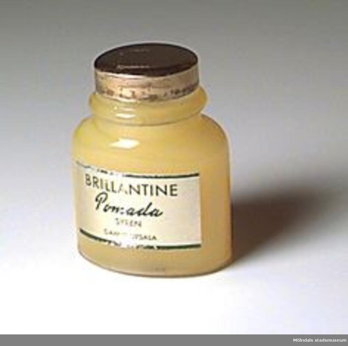 Oval glasburk med guldfärgat skruvlock. Innehåller gul pomada.Kjellberg arbetade i väveriet på Mölnlycke fabriker 1916-1969.