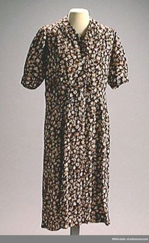 Brun klänning med orange, beige, gula och gröna blommor. Stoppad överallt.Selma Börjesson var född på 1890-talet i ett gråstenshus/backstuga i Hökekullen vid Hålsjön i Kållered. Hon bodde med sin syster. En bror levde på att fiska gäddor i Hålsjön och tog tillfälliga snickeriarbeten.Det var ett fattigt hem. Selma gifte sig aldrig utan bodde kvar i föräldrahemmet. Hennes bror Arthur byggde ett litet trähus vid sidan om stenhuset. Där bodde hon till 1960-talet då hon på vintrarna flyttade in i Brattåshemmet. Det fanns bara en gångstig fram till husen på 1970-80-talen.Selma var en sparsam, arbetssam och ordentlig kvinna. Inget slängdes eller fick förfaras.Hon hade klänningen på sig på ålderdomshemmet i Brattås och lappade och lagade den hela tiden.Hon dog i 90-årsåldern på 1980-talet.Gåvan förmedlad genom Staffan Bjerrhede som också lämnat uppgifterna.
