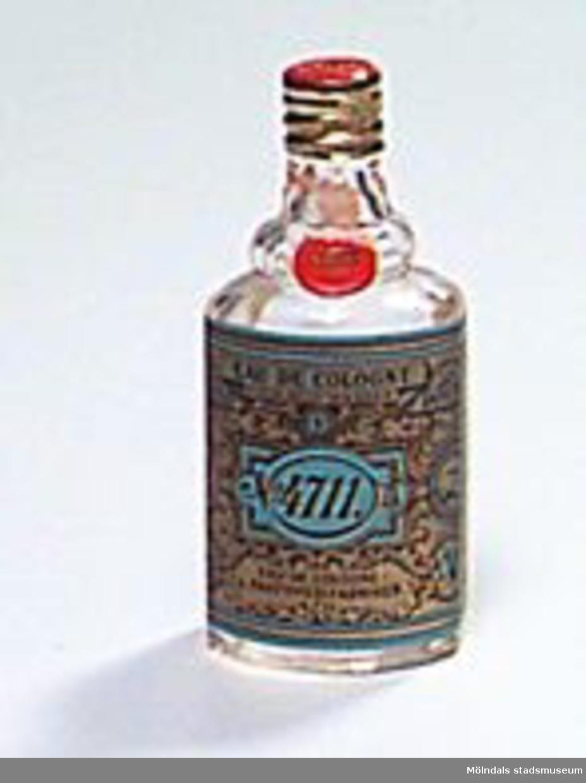 En liten genomskinlig parfymflaska i glas med en pappersetikett som är rikt dekorerad i guldfärg, svart och blått. Innehåll kvar i flaskan. Röd och guldfärgad metallkork.Det var troligtvis en italienare, Giovanni Feminis från Milano, som i slutet av 1600-talet startade tillverkningen av parfymer i Köln. Namnet 4711 står helt enkelt för numret på huset där parfymen tillverkades. I Tyskland används denna parfym fortfarande mycket. I Sverige köps ca 50.000 stycken 100-millilitersflaskor om året, lite jämfört med förr, och mest av äldre människor. Parfymen säljs fortfarande ifrån Köln.