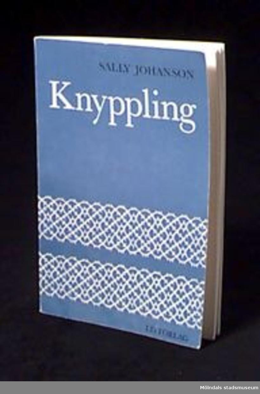 """Bok med titeln """"Knyppling"""". Handbok i knyppling av Sally Johanson. Blått omslag dekorerat med bilder av spetsar. 90 sidor."""