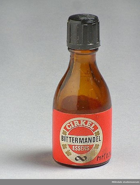 Flaska i brunfärgat glas för bittermandelessens, märke Cirkel.