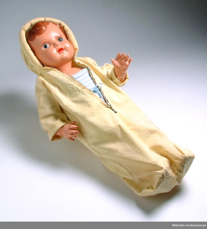 Åkpåse för docka, citrongul och med huva.Samhör med docka MM03872:1 och hängslebyxa MM03872:2.