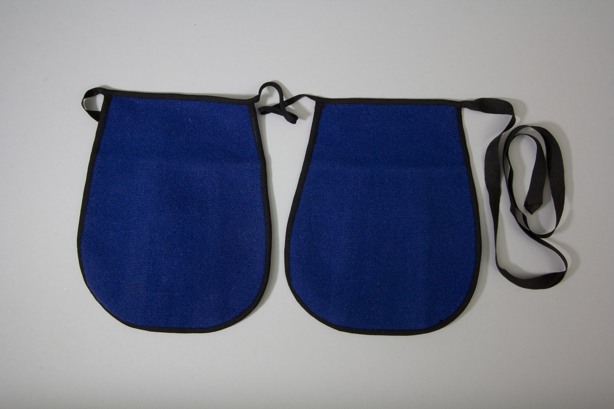 Kjolsäck till dräkt för kvinna från Östervallskog socken, Värmland. Modell med avskuret framstycke. Tillverkad av grovt, kanske handvävt tyg, tuskaft, i två färger. Framstycket gjort av tre delar, rött i mitten och och blått på sidorna. Ofodrat. Bakstycke och överstycke av blått tyg. Kantat runtom med svart diagonalvävt ylleband. Två stycken kjolsäckar fästa, en på var sida, på ett knytband diagonalvävt av ullgarn.