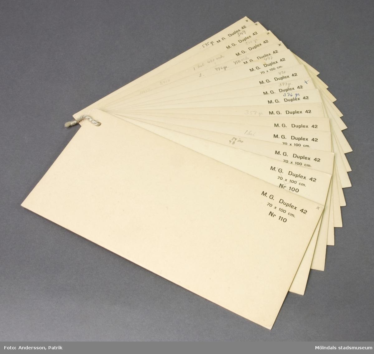 Prover med M.G. Duplex 42 kartong. Produktfakta på varje ark. Gulnade (vita) kartonger i olika gramvikter. Handskrivna anteckningar. Litteratur: Papyrus 1895-1945, Minnesskrifter, Esseltes Göteborgsindustrier AB, Göteborg 1945.