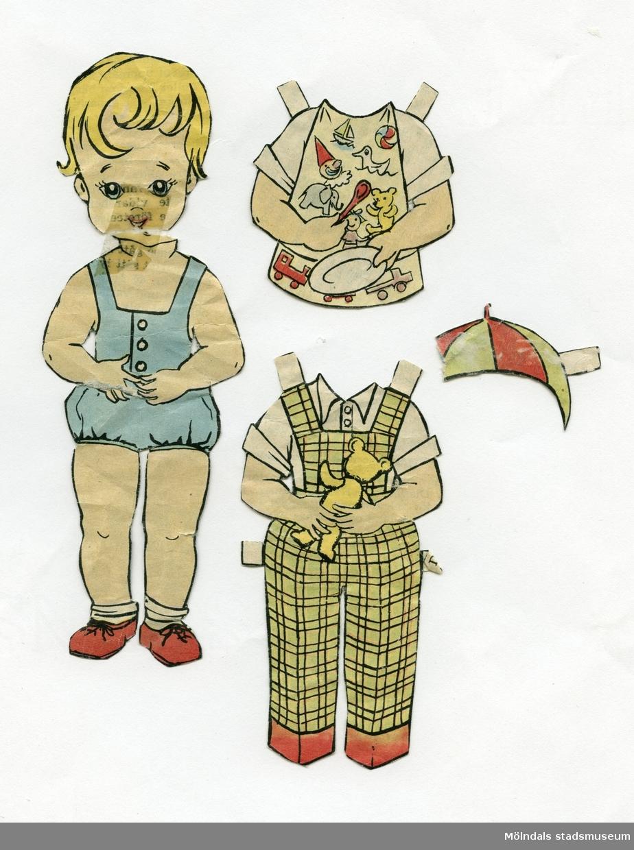 """Klippdocka med kläder, urklippt ur tidning på 1950-talet. Docka och kläder märkta """"Lasse"""" på baksidan - dockans namn. Dockan föreställer en liten pojke, med blont hår, iklädd lekdräkt med korta ben, strumpor och skor.Garderoben består av hängselbyxor med skjorta, skjorta med hakklapp, tallrik och sked, samt mössa (saknas en bit)."""