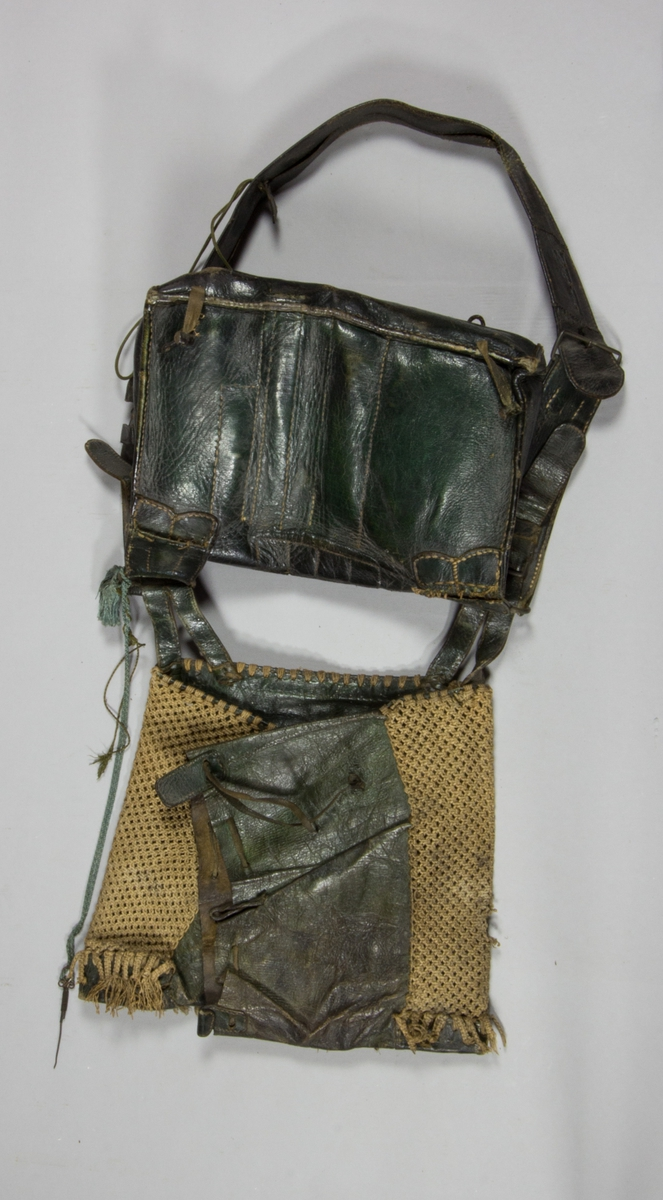 Jaktväska av läder med axelrem. Under väskan en läderpåse för bytet, täckt med flätning. Väskan, med lock, innehåller ett flertal fack för kruttyg m.m. På själva locket fyra små fack för flintor (tre flintor ligger i väskan), i väskan åtta fack för hagel, kruthorn, oljeflaska m.m, och utanpå väskan två fickor med lock med respektive två och tre fack. I bärremen sitter små fickor med krutmått samt liten benskiva, rund med hål, samt i snoddar fästade vid remmen två instrument av mässing.