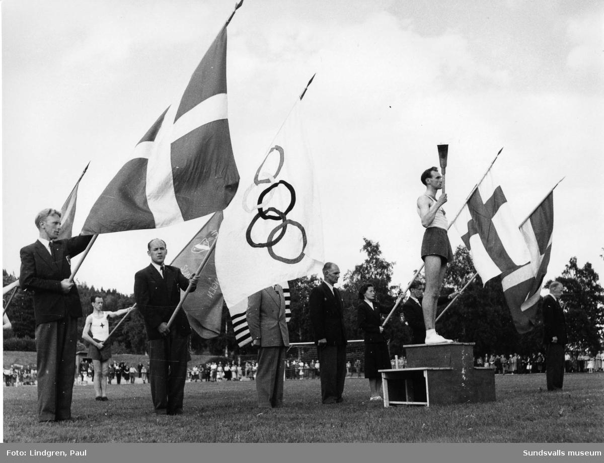 Den olympiska elden passerar Sundsvall.  Programmet för den olympiska eldens framförande på söndag genom våra trakter samt för den högtidlighet med vilken den på söndagmiddag skall hälsas välkommen i S:valls idrottspark och sedan sändas vidare. Det blir både militärmusik, högtidstal, fanparad och idrottstävlingar som skall omrama ceremonin inne på planen, dit facklan föres av IFK-löparen Eric Nilsson. Efter det högtidligaste inslaget föres så facklan ut av kämpen John Nyman, varefter dess färd går vidare till Kramfors över Härnösand.