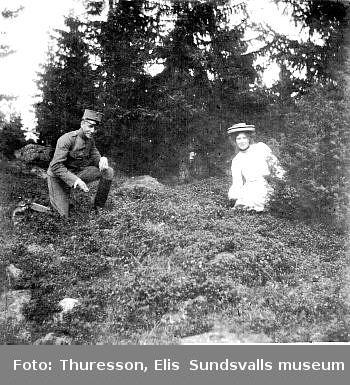 Man, iklädd militäruniform, och kvinna i skogsbacke.