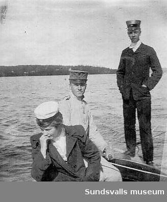 Två män, varav en i militäruniform, och en kvinna i båt.