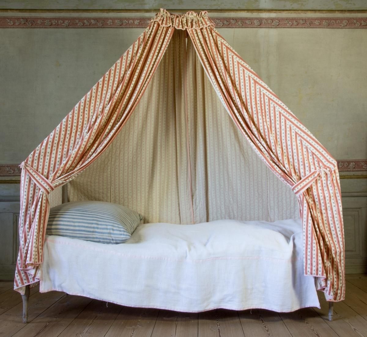 Sängklädsel tillverkad av bomullstyg med tryckt mönster, långrandigt. Ränder i rödrosa med brun sicksackrand omväxlande med rader av enkla småblommor i brunt. Modell där främre och bakre förhängena är formsydda efter stommen och fastsydda i ett överstycke som vilar löst på sängens överdel. Sängklädseln är inte fäst i sängen. Omtag vid de främre förhängena. Runt sänghimmeln sitter en veckad volang. Volang, omtag och förhängen är kantade med ett rosa bomullsband.