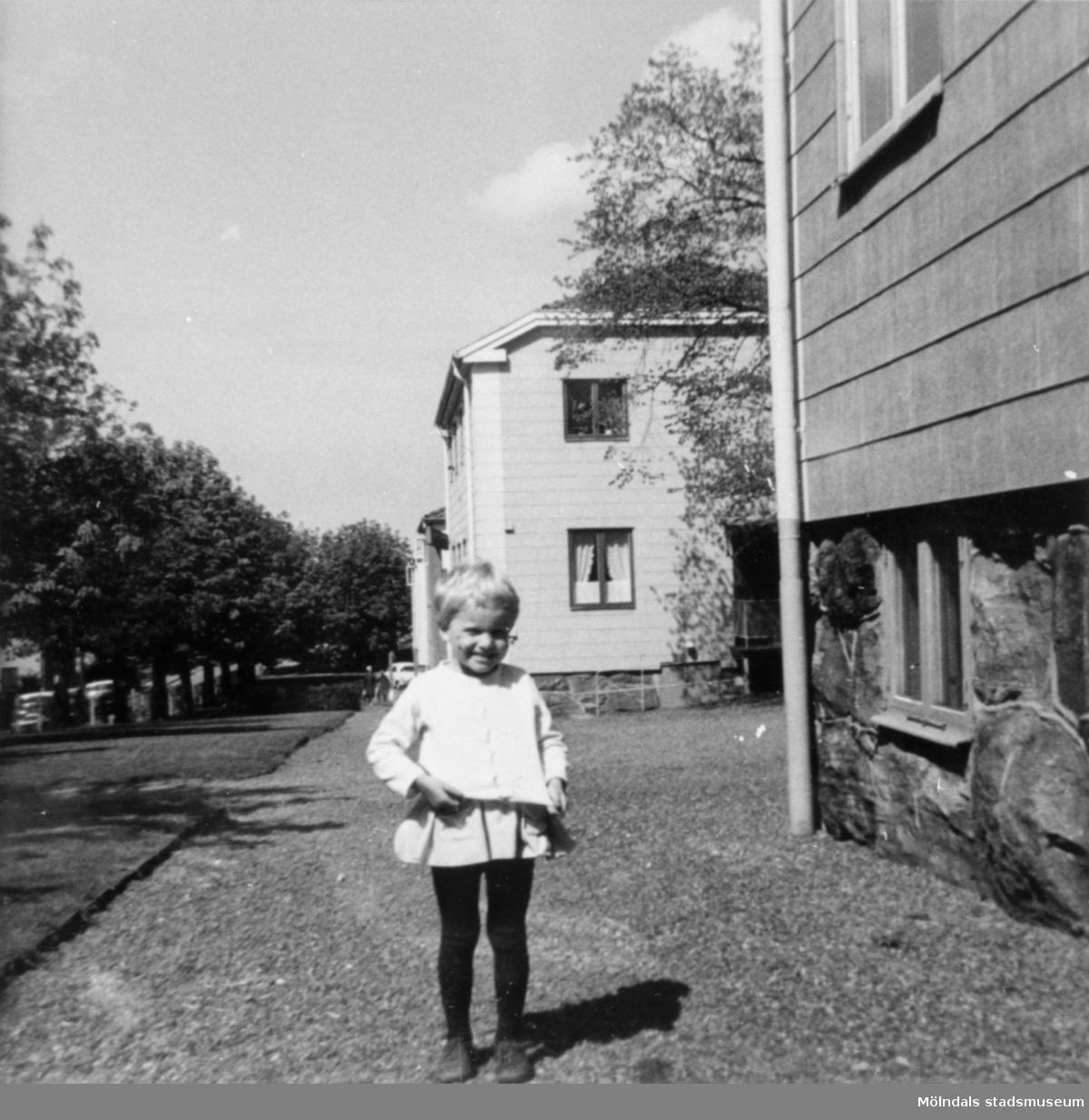 En liten flicka som står utanför papyrushusen på Brunnsgatan (1-9). 1960-tal.