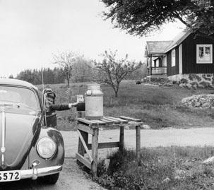 Bilkåkande lantbrevbäraren Cyril Falk på linjen Lönsboda-Hunshult-Björkhult-Lönsboda. Brevlåda i Hunshult får post.  Foto maj 1961.