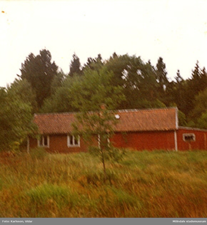 Ett rödmålat bostadshus, ett och ett halvt plan, som ligger på en kulle. Ort och årtal är okänt.