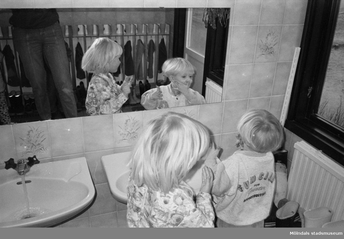 Två små barn står framför en spegel och tvättar sina händer och mun i handfatet. I bilden speglas fröken som står strax bakom. Väggen bakom handfatet är kaklat med bl.a blom-dekor. Katrinebergs daghem.
